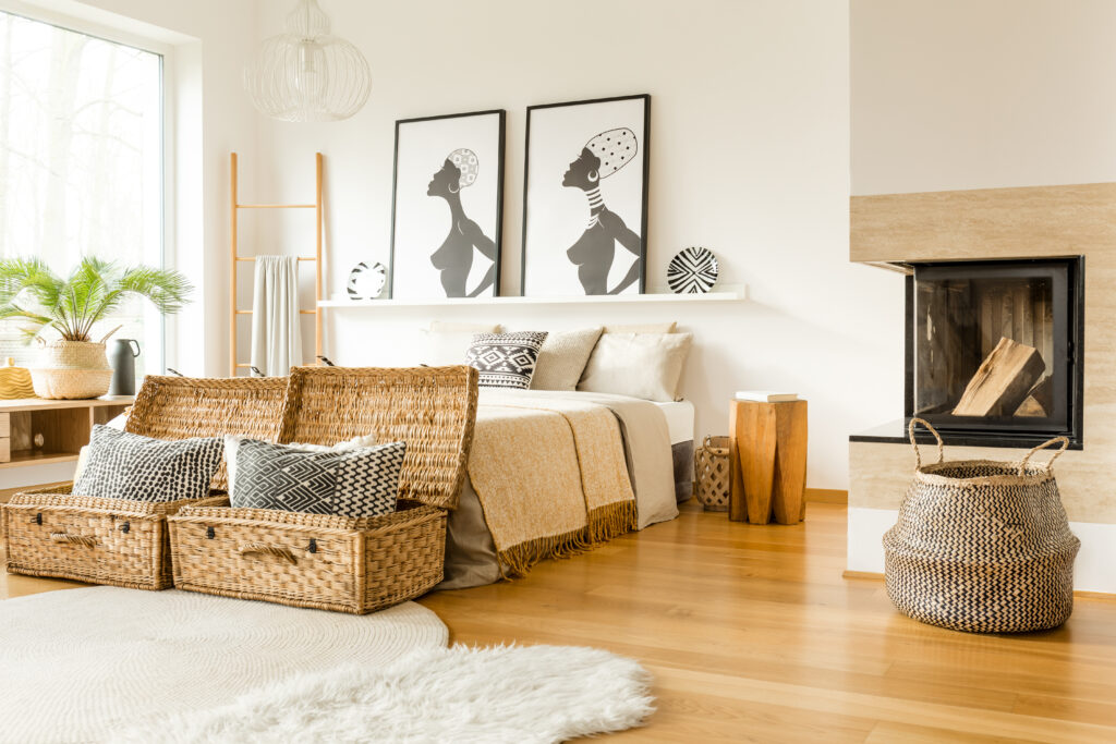 Fireplace, wattle boxes with pillows, bed and African posters in a boho bedroom interior