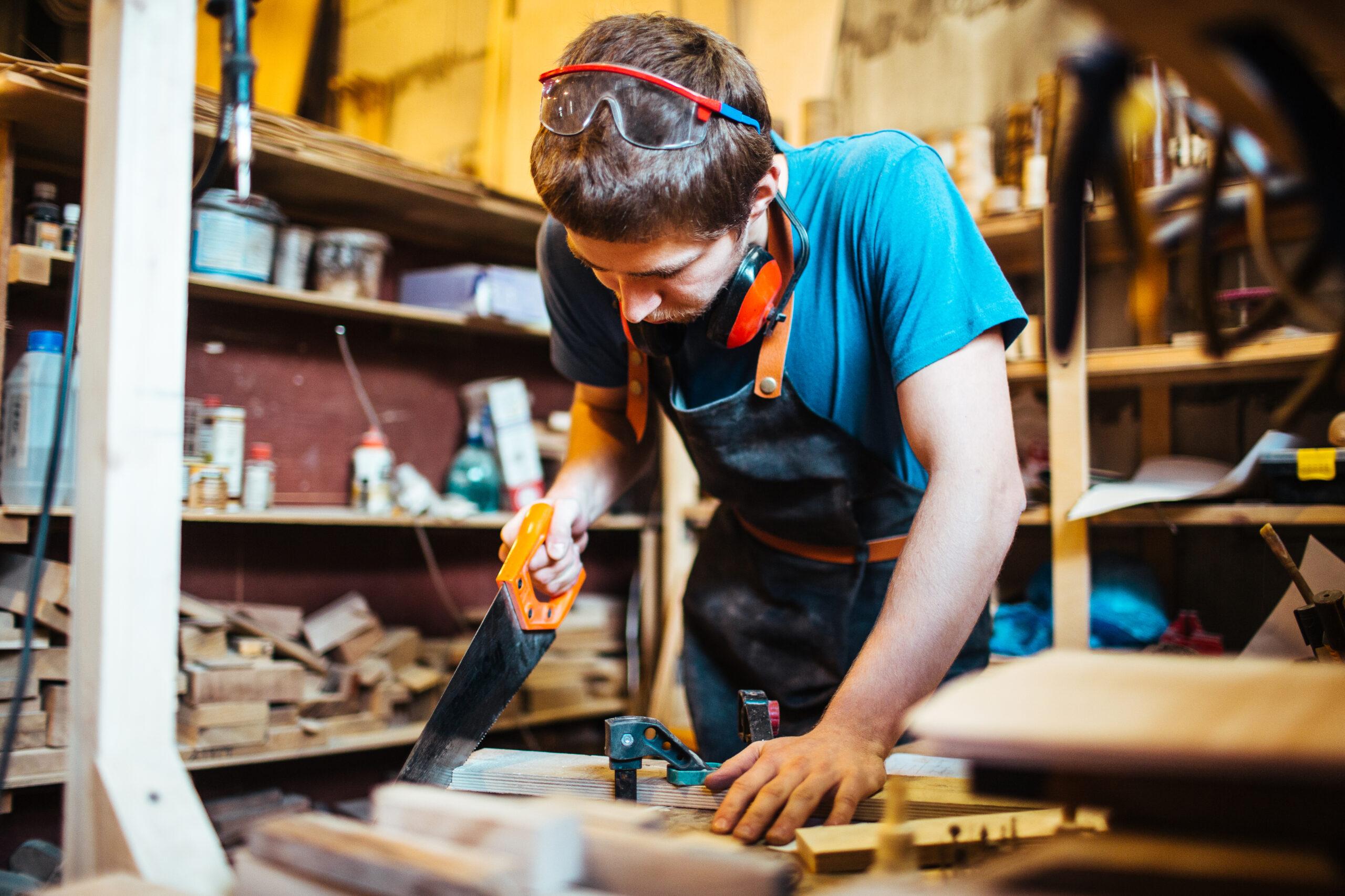 Modern handyman sawing wooden board in his workshop