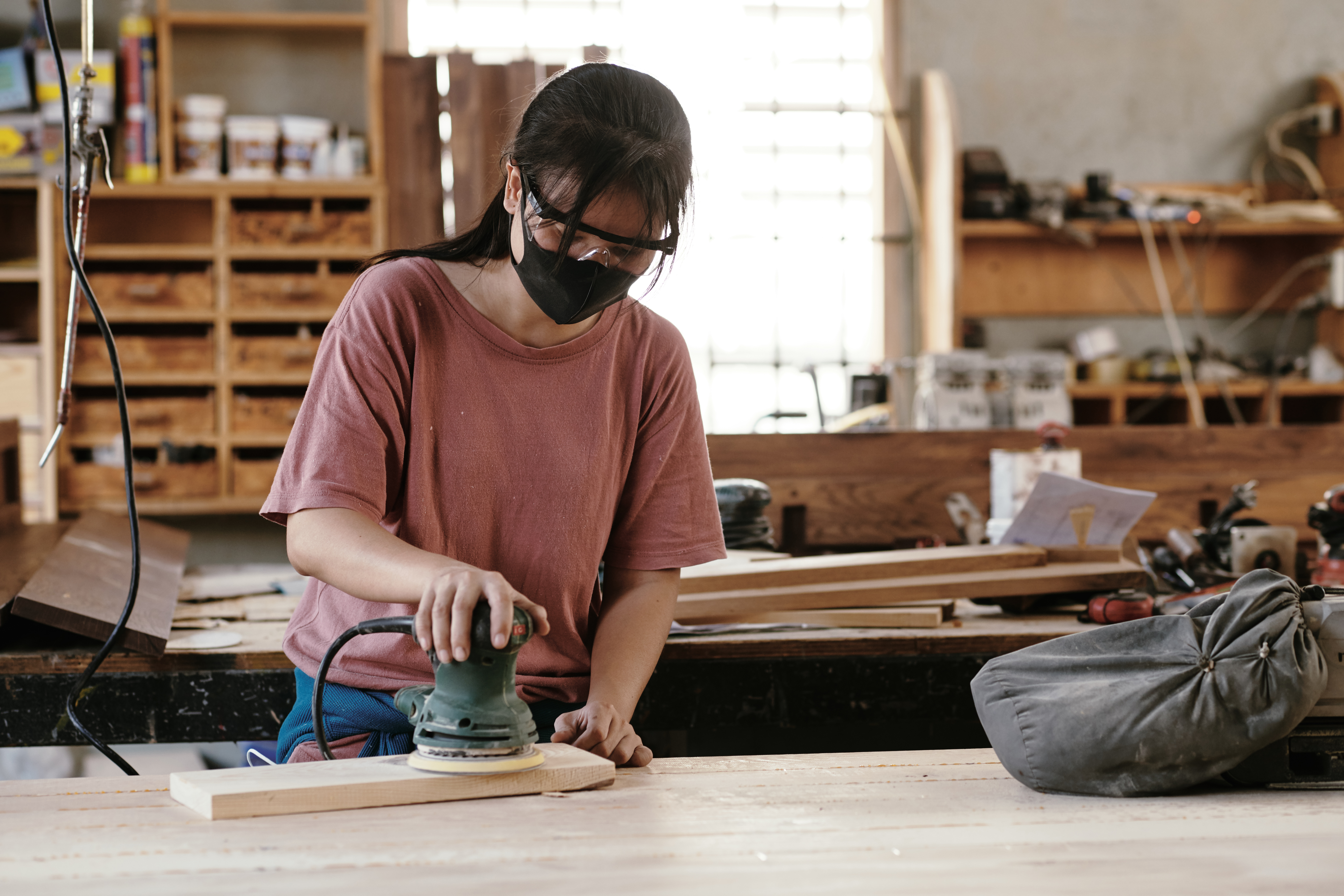 Young female carpenter in protective mask and goggles sanding wooden board