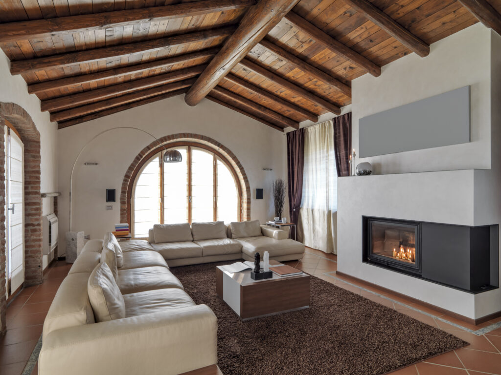 foreground of a leather sofa and  fireplace in the modern living room with tile floor and wood ceiling