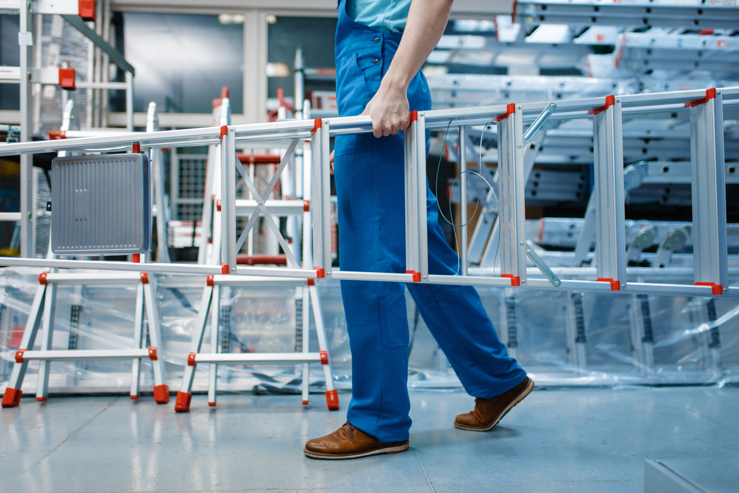 Male employee in uniform holds new aluminum stepladders in tool store. Department with ladders, choice of equipment in hardware shop, instrument supermarket